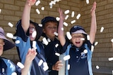 A group of laughing and smiling young students throw styrofoam beads into the air outside their classroom.