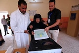 An Iraqi elderly woman casts her ballot, assisted by two men.