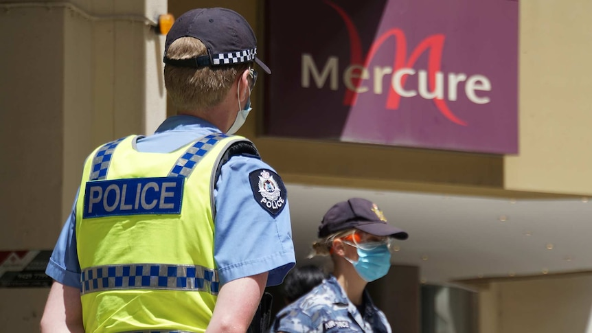 A police officer and an Australian Border Force officer stand wearing face masks outside the Mercure Hotel in Perth.
