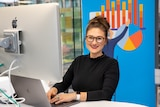 Employee Kirsti Taylor sits at her computer at her employer's new office.