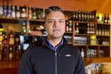 Lachhu looks directly into the camera, his bar behind him with bottles on shelves.