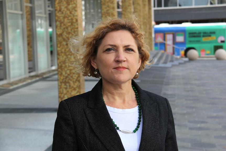 A woman with curly hair in a suit stands in an outdoor square.