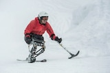 Hari Budha Magar in a red ski jacket skiing in snow using a seat like single ski and two smaller hand held skiis on poles