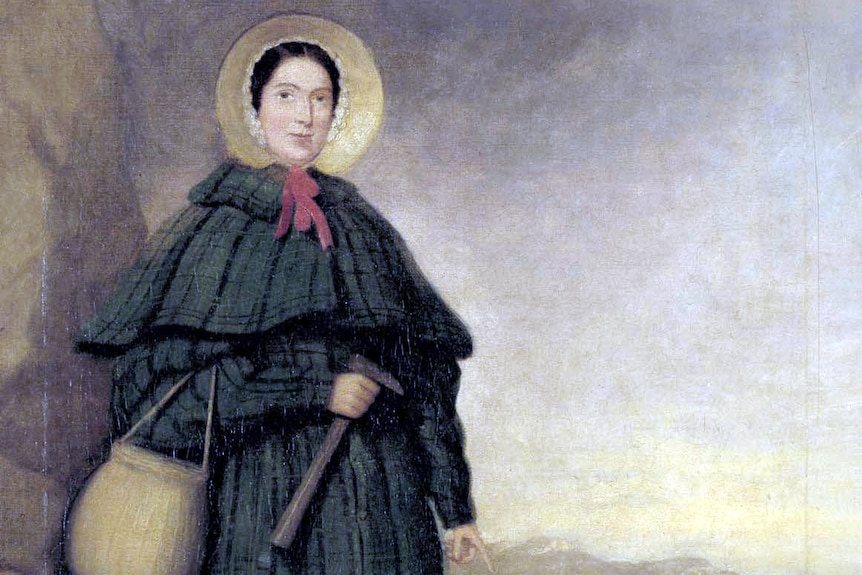 A portrait of Mary Anning wearing a cloak, bonnet and carrying a pick and basket while standing on the beach.