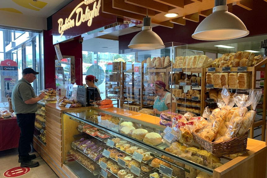 A man shops at a bakery with cashiers behind plastic shields.