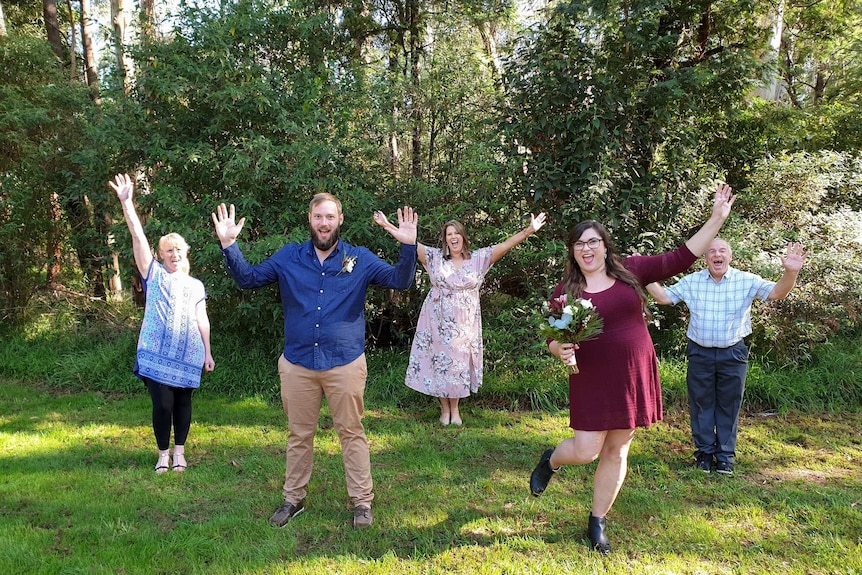 Five people stand in a pattern and separated from each other on the grass with trees behind them holding their hands in the air.