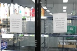 Milk fridges in a supermarket are almost empty with signs on the doors limiting customers to one bottle each