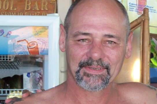 Gregory Robbins smiles at camera with tatoos on his chest.