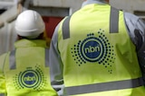 Two figures with hard hats and NBN vests look away from the camera