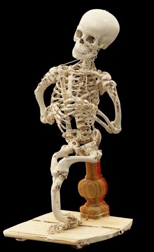 A seated skeleton holding a wooden recorder.