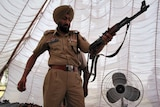 Punjab police officer with seized rifle