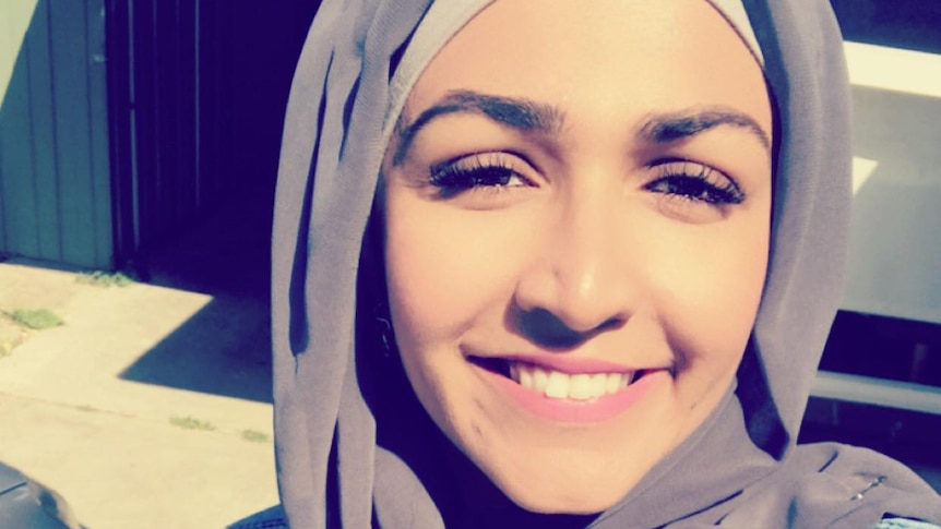 A photo of Anam Javed wearing a grey hijab and smiling.