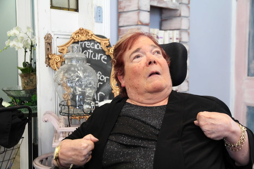 Betsy White sits in her wheelchair, she has red and blonde short hair and is wearing a sparkly black dress.
