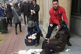 A security guard assists an injured woman on the steps outside a building in Brussels.