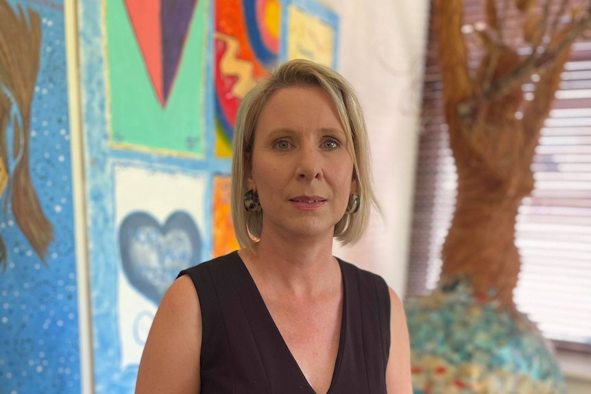A woman wearing a black dress stands in front of colourful artwork
