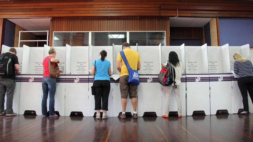 A row of people fill out forms at a polling booths during the Federal election.