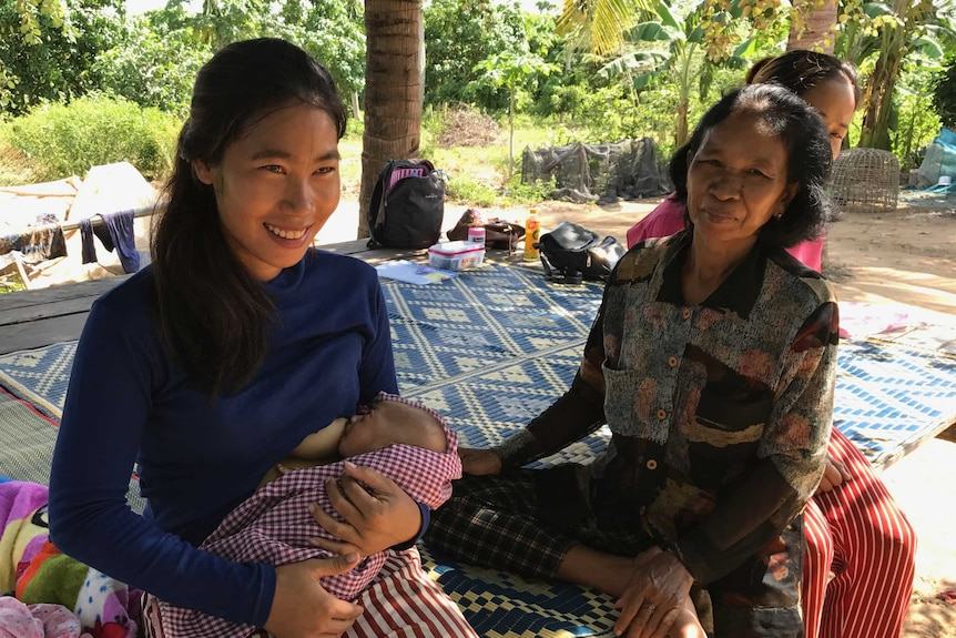 A young woman breastfeeding a baby with an older woman next to her