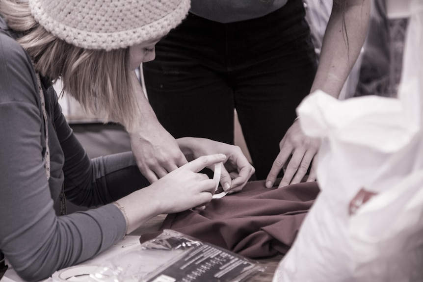 A person sews a piece of fabric
