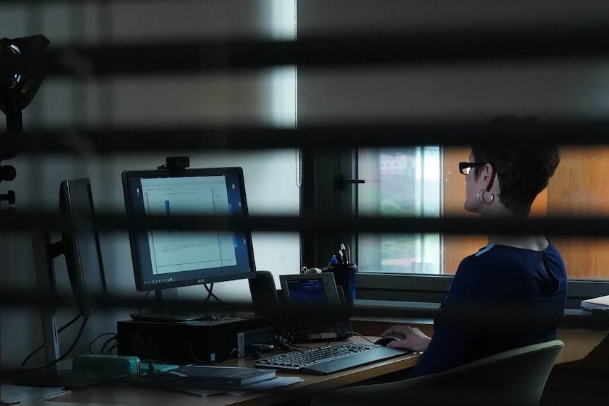 A woman sitting at a desk works on her computer