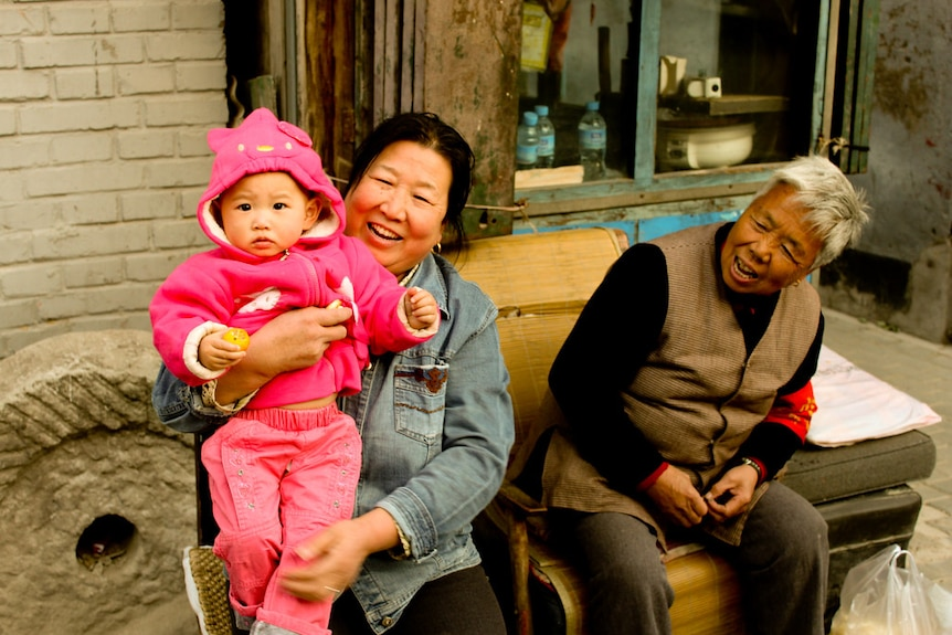 Three generations of women sitting and smiling
