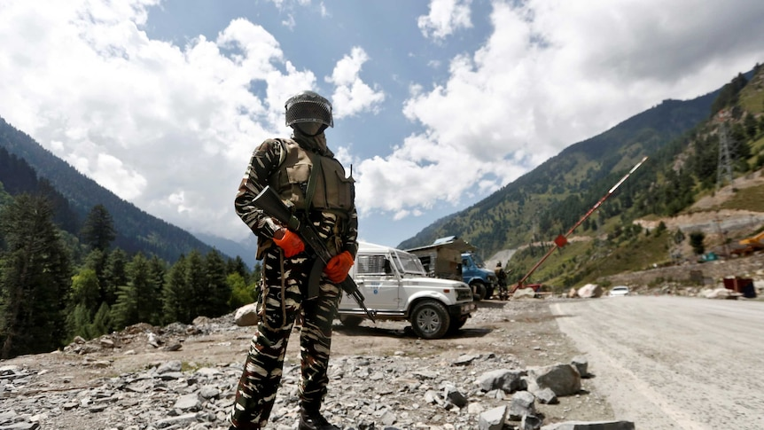 A man in army fatigues stands in front of a jeep and mountains.