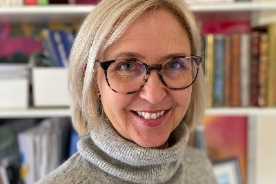 a woman in glasses smiling