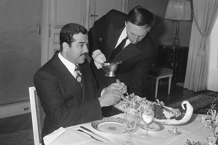 Black and white photo of Saddam Hussein lunching in Paris.