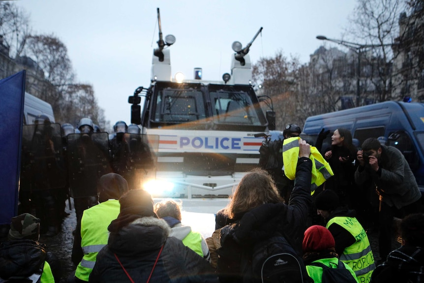 Demonstrators sit in front of a police water cannon on the Champs-Elysees avenue.