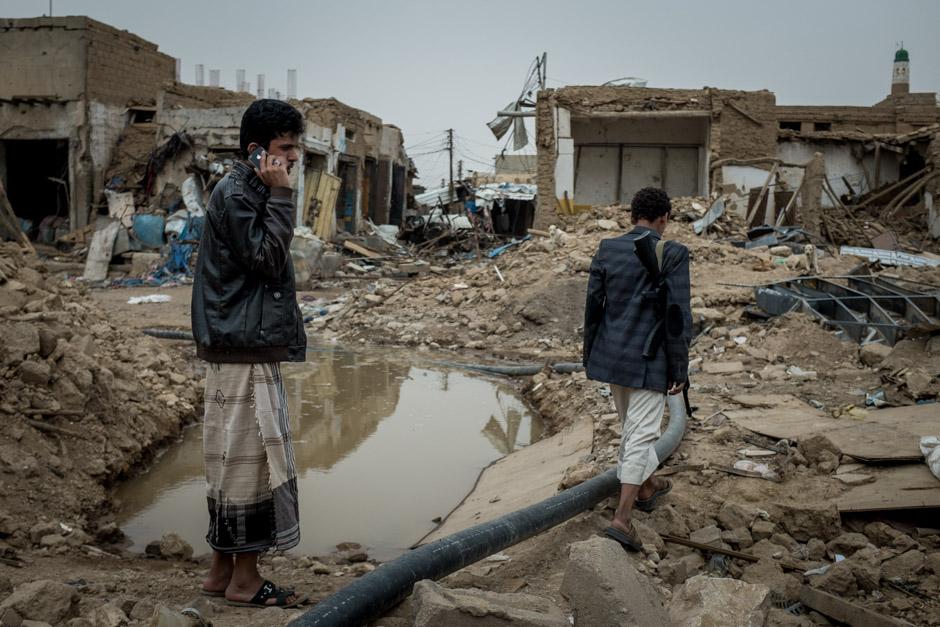 Two men walk through the ruins of the city of Sada'ah.