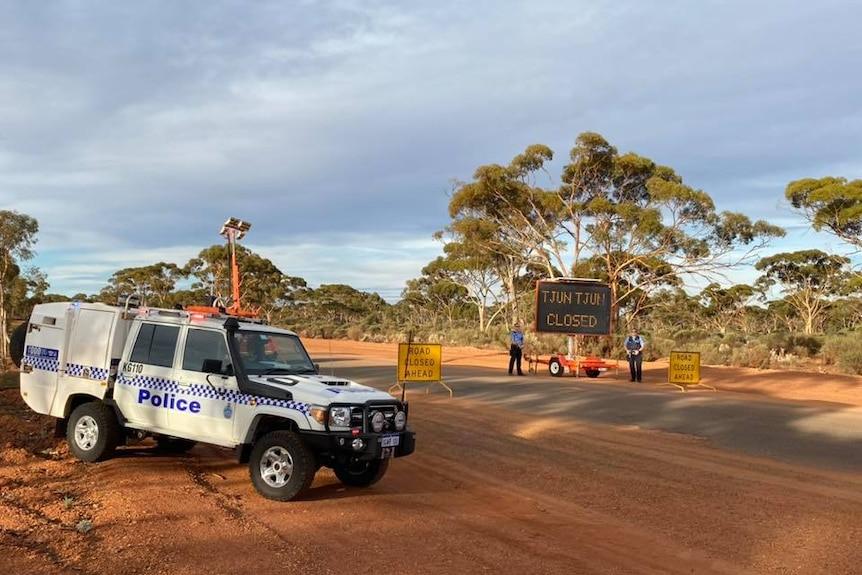 A police car is parked on the side of a dirt road, with two police officers standing next to a sign.