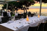 An empty waterfront restaurant table at dusk