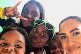 Tahnee Jash and four Indigenous children smiling and making hand signals at camera.