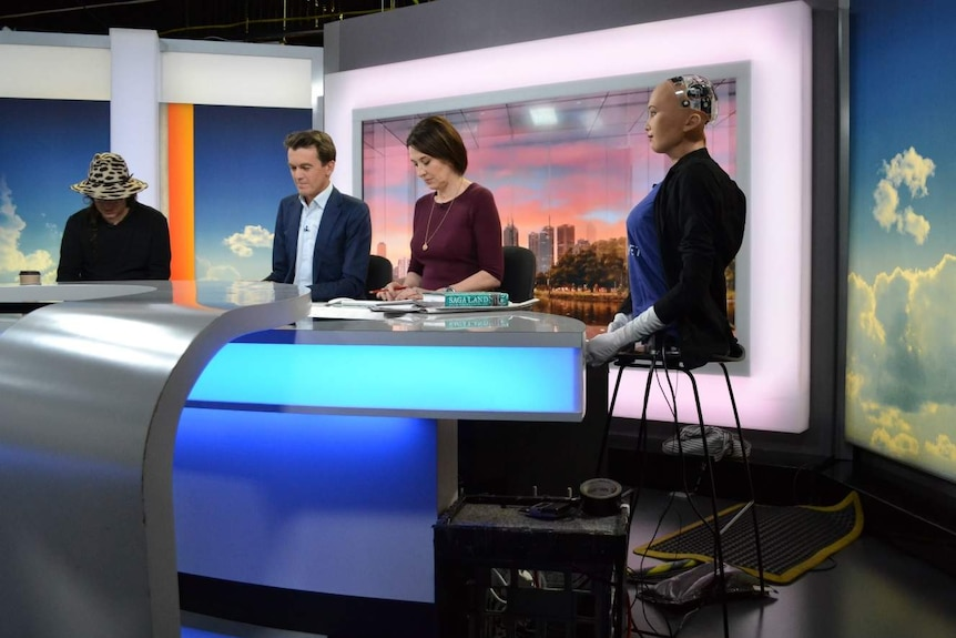 The torso of Sophia the robot sits on a stool at the news desk alongside the presenters and her creator.