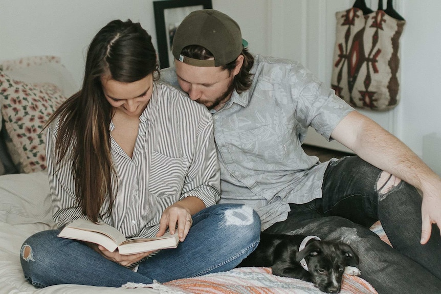 A couple sitting on a bed lovingly and looking at a baby names book, for a story about unique baby name popularity.