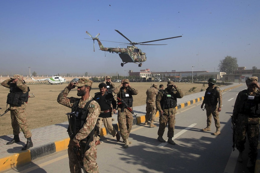 Soldiers holds their caps as a helicopter flies past during an operation near Bacha Khan University in Pakistan.