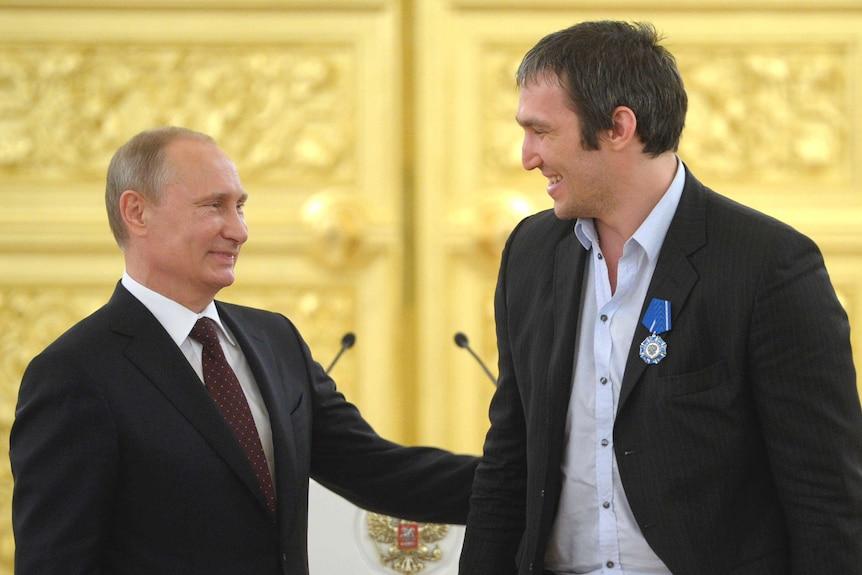 Vladimir Putin puts an affectionate hand on Alexander Ovechkin's arm