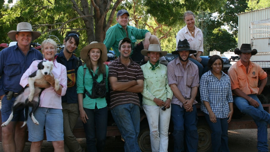 Owners with nine backpackers at Sutherland Station posing for a photo under the shade of a tree