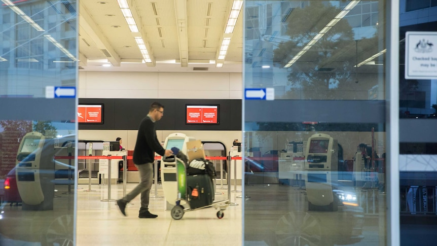 A man walks across an empty check-in area with a trolley bags on a trolley
