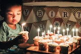 A young boy holds a birthday cupcake for a story on people pulling out of kids' parties