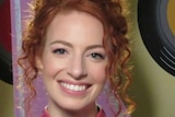 Emma Watkins wearing a colourful orange, blue and purple shirt, pictured against a colourful set with big records painted on it