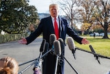 President Donald Trump speaks as reporters hold microphones