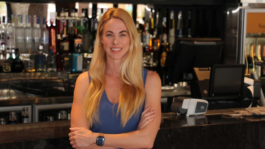 Bree stands behind the bar with her arms folded, smiling.