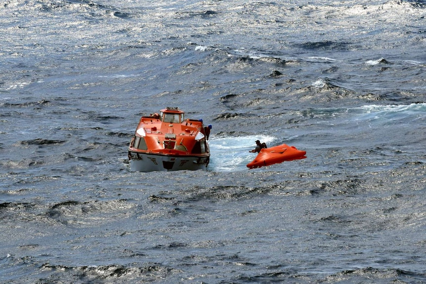 A rescue boat is beside a small life raft at sea