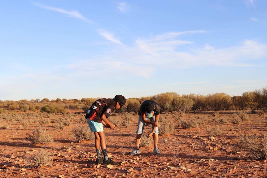 Two young boys bend over red, rocky ground.