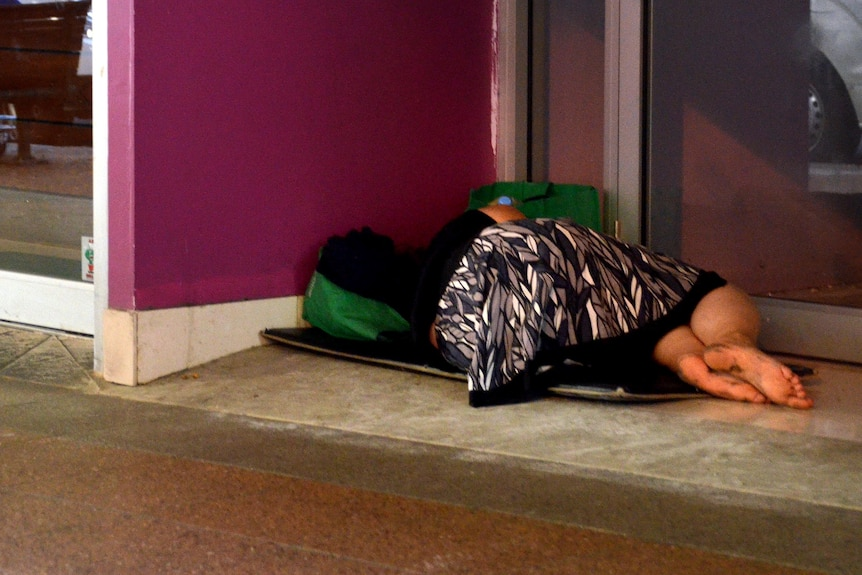 A homeless woman lies in the doorway of a business in the Brisbane CBD