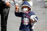 A child holding a parent's hand and clutching a toy rabbit wears a face mask.