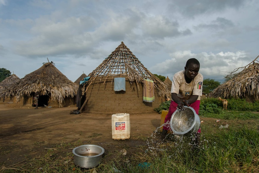 A woman carries a bucket outside her home in Kudo village, South Sudan.