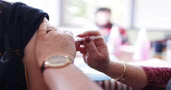 Nurse injects vaccine into arm