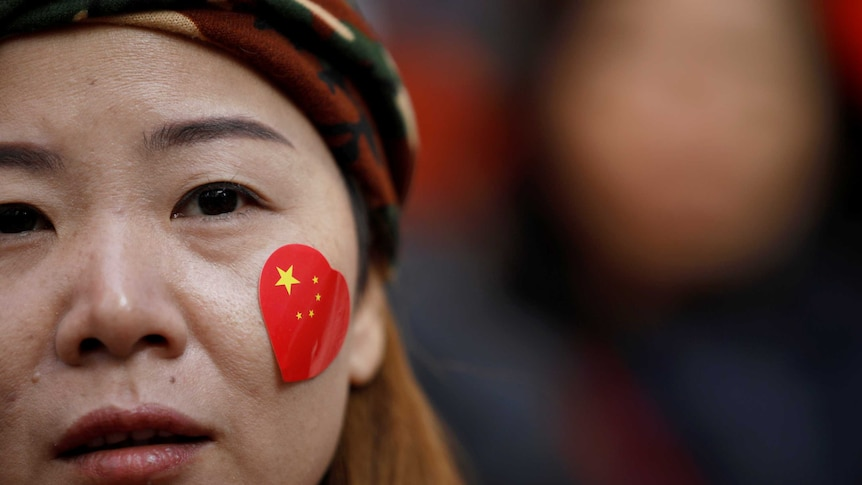 A close up of a woman's face with a heart-shaped sticker of the Chinese flag on her cheek.
