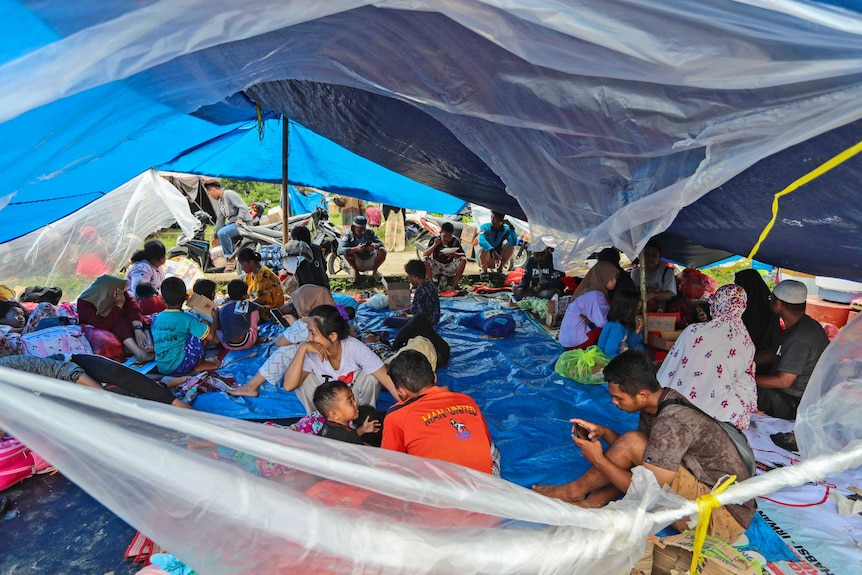 A large group of people sit on a blue sheet under a makeshift tent rigged with tarpaulins.